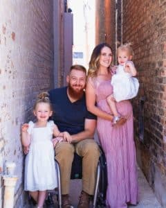 Kaleb, in wheelchair and Brittany Wilson pose outside with their two young daughters, all smiling