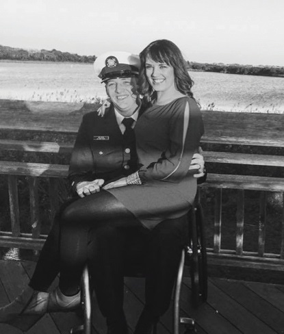 Kaleb Wilson in wheelchair on a pier with his wife in his lap