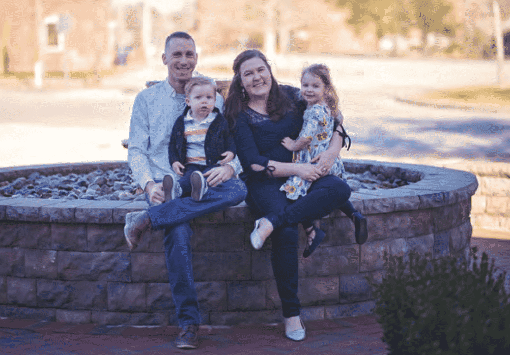 Caitlin Emmons pictured sitting on side of fountain with husband and two small children
