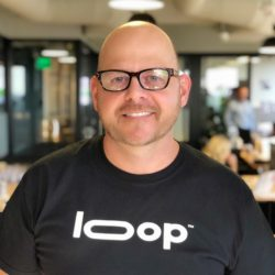 Shawn Driscoll smiling wearing a black and white t-shirt with the word Loop on it
