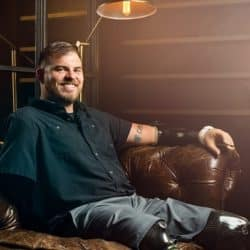 Travis Mills seated on couch wearing two prosthetic legs smiling