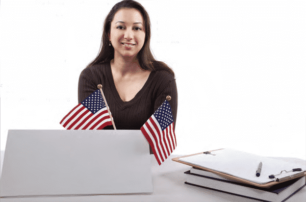 A woman smiling with a laptop and two small American flags in front of her