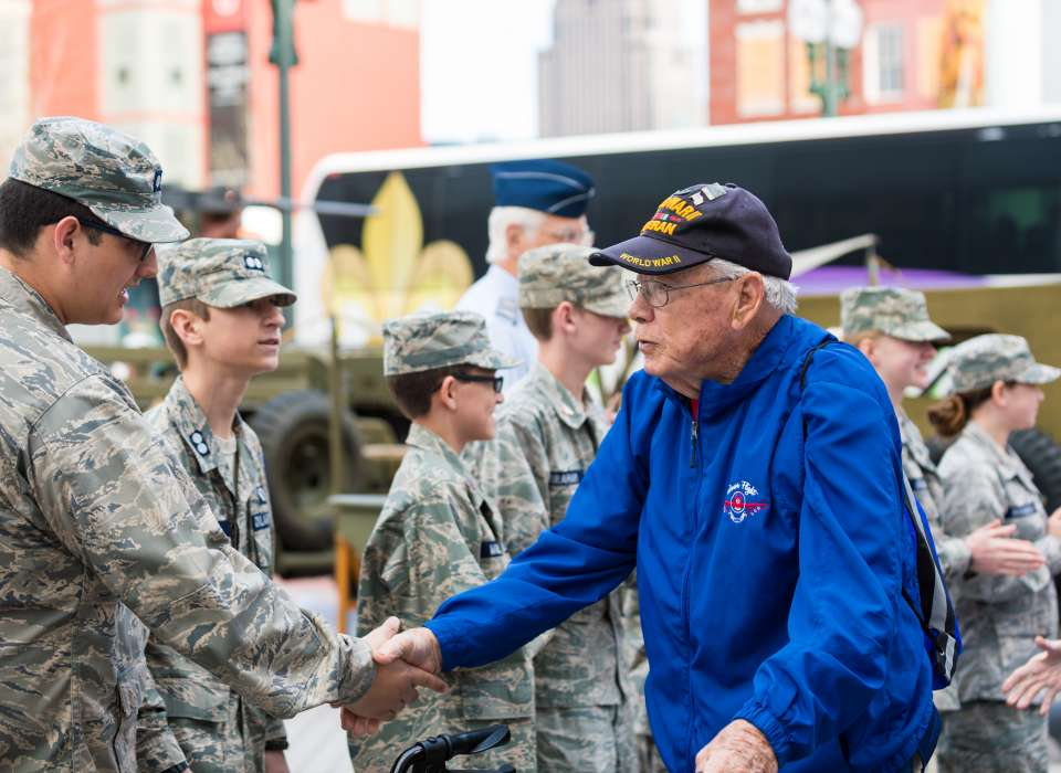 older veteran shaking hands with a group of younf soldiers in uniform