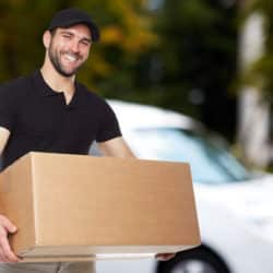 Smiling delivery man holding a paper box