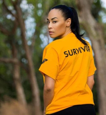 Brandi Benson looks back at camera over her shoulder wearing a survivor shirt