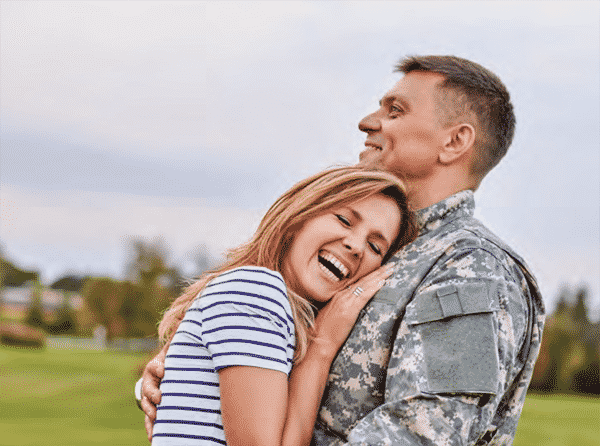 man in military fatigues hugging his wife smiling