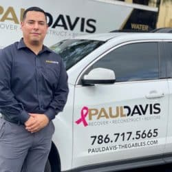 Edison Recinos stands in front of his Paul Davis work vehicle smiling