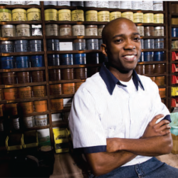 Young African-American man seted with armed folded smiling in a small goods store