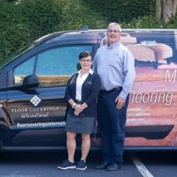 Bill Mahoney and Marie Mahoney stand outdoors in front of their decorated work vehicle smiling