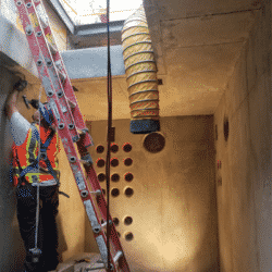 man woring in protective vest working on construction site near a ladder