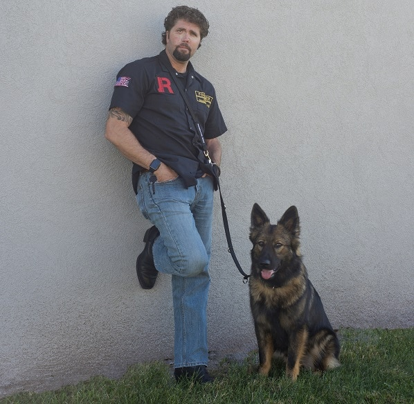 Former Navy SEAL Jason Redman and service dog Kharma stand next to each other on the grass