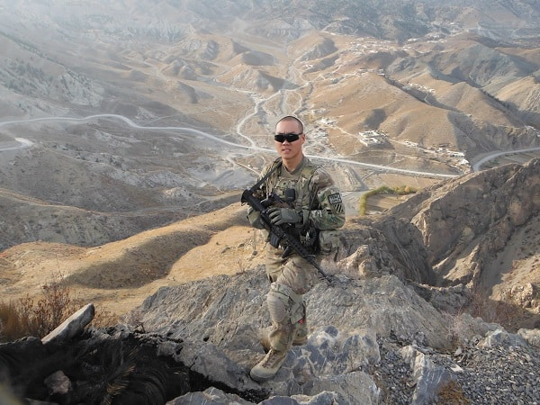 Paul Yoon pictured in Army uniform holding a rifle standing in rough terrain