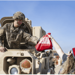 young girl with Christmas cap on hands soldier in a tank a gift bag