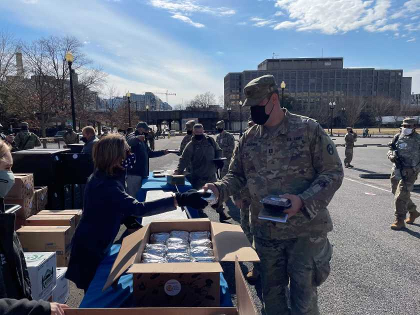 National guard wearing a black protective face mask takes a plate a food from a food booth outside Capitol Hill