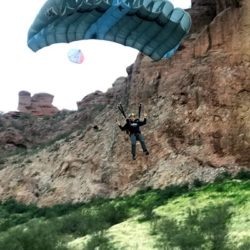 us marine lands his parachute in grassy area near mountain