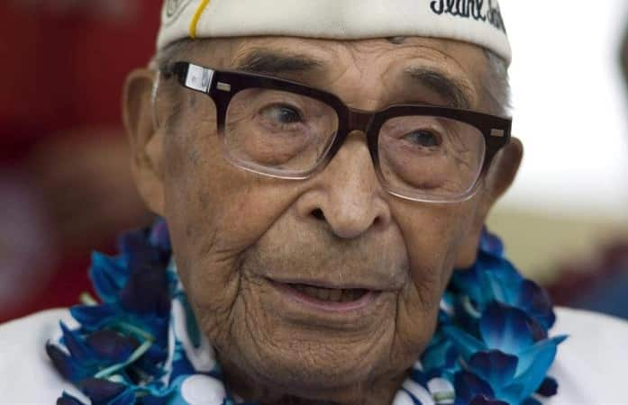 Ray Chavez, oldest Pearl Harbor vet, smiles at 106th birhday party wearing a lei
