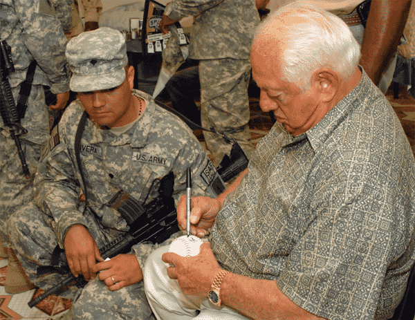 Tommy Lasorda visits with a U.S. Soldier and autographs a baseball for him