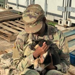 US Soldier holding her puppy while sitting on the ground