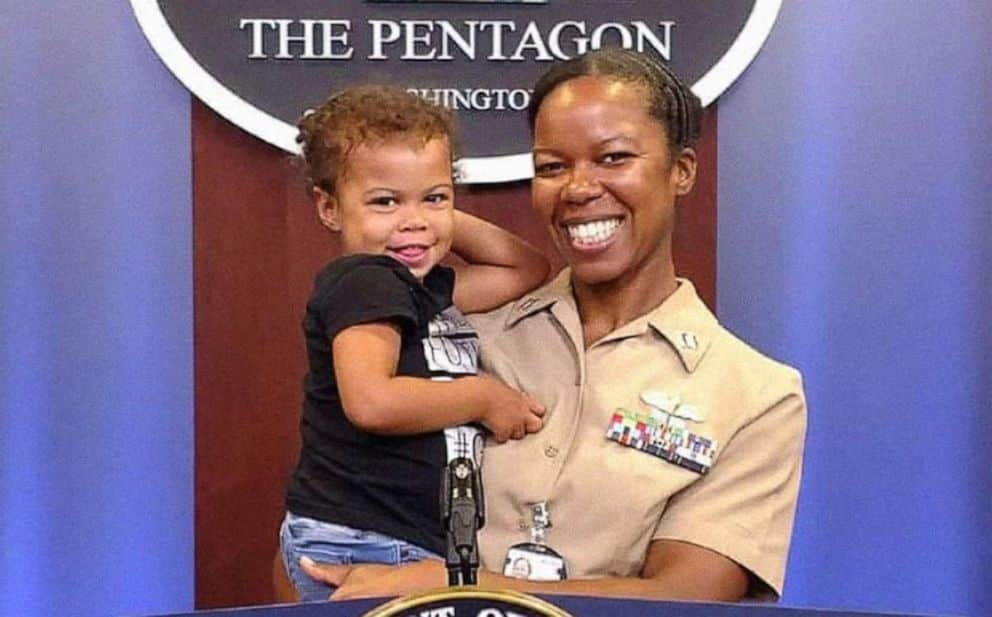 Thereasa Black in military uniform holds her young daughter in her arms with the Pentagon sign in the background