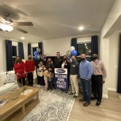 Service-disabled war veteran stands with family and friends in side the livingroom of his new home