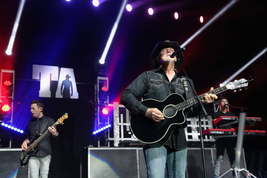Trace Adkins performs in on stage with his guitar in blue jeans, cowboy style shirt and cowboy hat