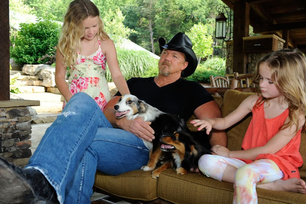 Country music star Trace Adkins, with his daughters Brianna and Trinity, and his dogs Bella and Daisy sitting on a couch