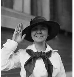 woman smiling waving hand wearing a large brimmed black hat and Navy Uniform circa 1917