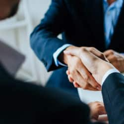 two business people shaking hand during meeting