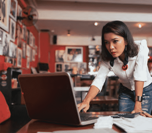 business woman leaning towards table with her hand extended on keyboard interested in an open laptop