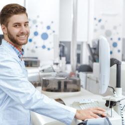 young male laboratory technician operating computerized equipment