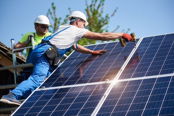 Two workers technicians installing heavy solar photo voltaic panels to high steel platform. Exterior solar system installation, alternative renewable green energy generation