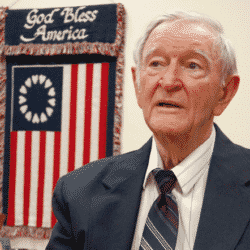Charles Coolidge looking left in suit and tie with an american flag in the background