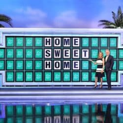 Wheel of Fortune puzzle board with Home Sweet Home written on the board. Pat and Vanna are standing in front of it and smiling.