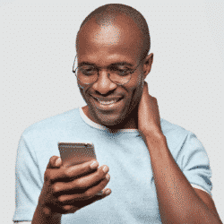 man wearing glasses and holding cell phone up to face