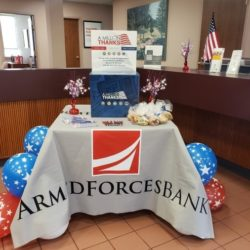 table decorated in military colors inside bank lobby with Armed Forces Bank banner on it