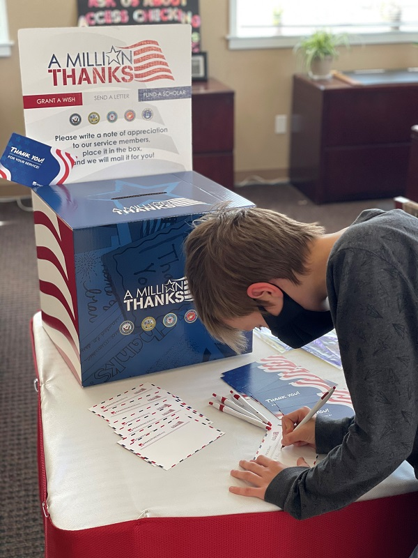 table decorated in military colors inside bank lobby with young man filing out a card to drop in box