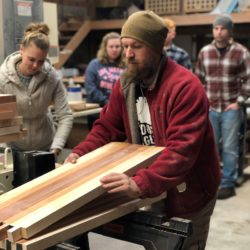 woodworking students move large piece of lumber on to skillsaw