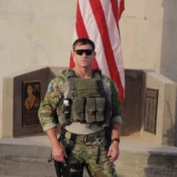 man in army service attire standing in front of U.S. flag