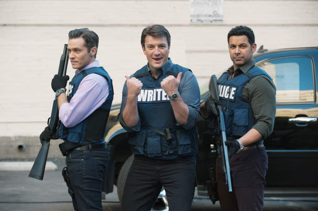 Three men outside on a a show set. They're all wearing police vests and the middle man is pointing towards the two of them.