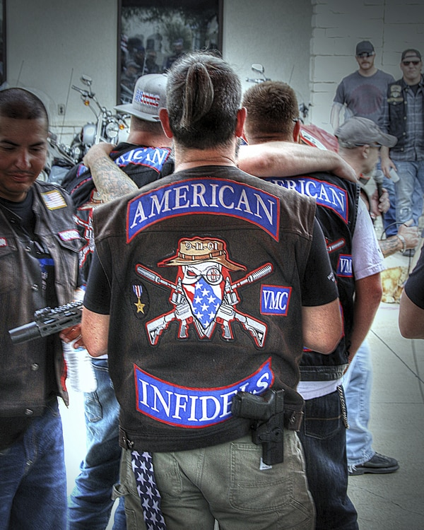 The back of an American Infidels motorcycle club member jacket displayed on man in group of other riders greeting each other in a room