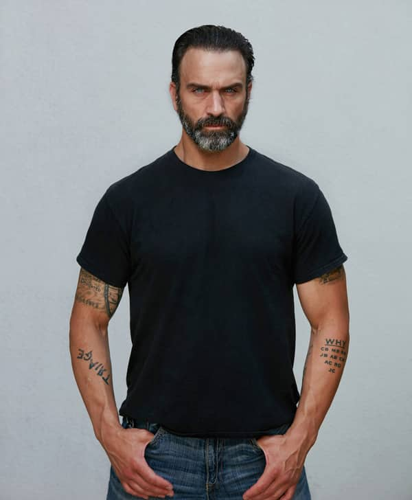 Jeff Bosley in rugged jeans and tee-shirt modeling look with thumbs in pockets