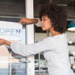 Pretty business owner putting up her open sign
