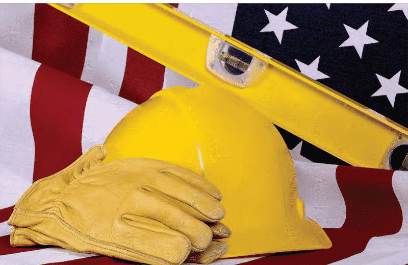 construction hard hat, glove and level pictured with us flag