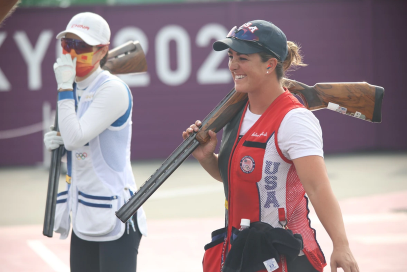Gold medal winner 1st lt. Amber English and competitor walk together while holding their skeet shooting rifles