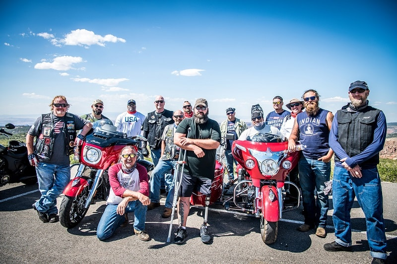 Group of motorcycle riders gather around two mororcycles and a disabled veteran with a prosthetic leg
