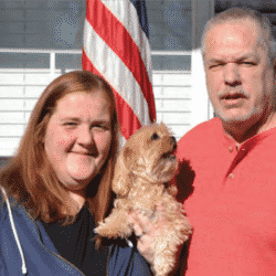 The Nutt family smiling outside their home with US flag in background
