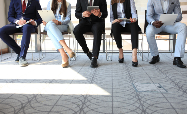 five job interviewees seated in chairs wating for job interview