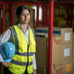 female warehouse worker with helmet and safety vest.