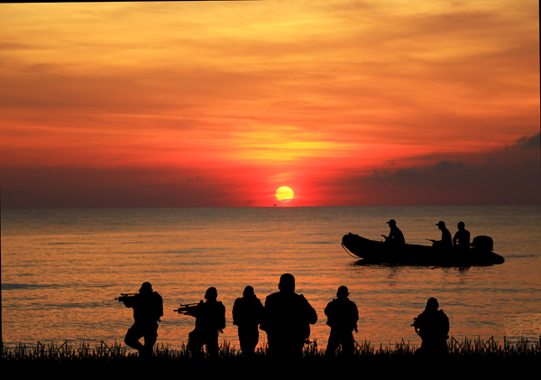 Navy seal on land and in small boat silhouettes on sunrise