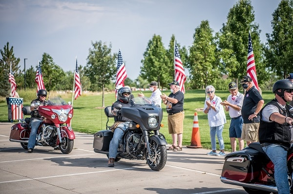 Group of motorcycle riders gather around two mororcycles and spectators on the sidelines
